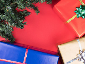 Christmas gift boxes and christmas tree on red background. Tradition ornament.