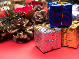 Christmas gift boxes wrapped in different colors under christmas tree on red background. . Festive interior decor.
