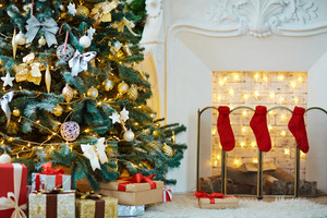 Christmas tree, gift-boxes and tree red socks by fireplace in room prepared for holiday