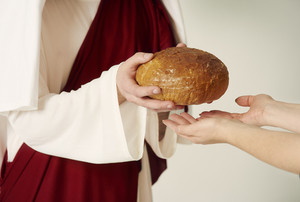 Christs hands handing over loaf of bread