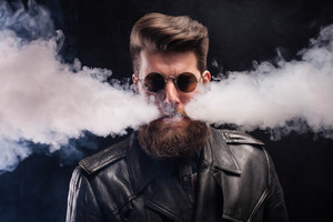 Cigarette smoking coming out of attractive man mouth with cool beard over black background. Bearded man . Handsome man.
