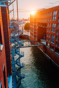 Circular staircase, bridge over canal and red brick buildings in the old warehouse district Speicherstadt in Hamburg in golden hour sunset light, Germany. View from above