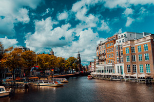 City view of Amsterdam with cruise boats and typical brick houses on sunny day with Vibrant fluffy clouds