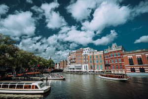 Classical Amsterdam cityscape. Cruise boats floating on the channel, river side promenade, cafes, typical Dutch architecture. Urban scene and white fluffy clouds