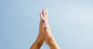 Clean well manicured hands of a young woman, applying hand cream, skin care on light blue background