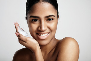 cleansing skin concept. smiling woman with a foam on a hand