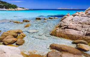 Clear amazing azure and turquoise colored sea water with huge granite rocks in Capriccioli beach, Sardinia, Italy