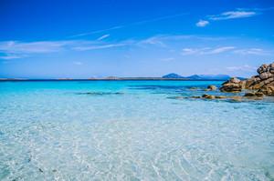 Clear amazing azure coloured sea water with granite rocks in Capriccioli beach, Sardinia, Italy