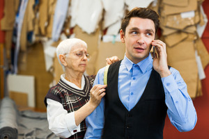 Client of dressmaker talking on cellphone in tailoring-shop