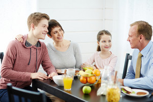 Close-knit family gathered together in kitchen, talking to each other animatedly and eating healthy breakfast, waist-up portrait