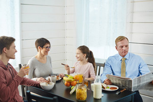 Close-knit family of four enjoying delicious breakfast at home: they sitting at kitchen table, eating cornflakes and chatting with each other