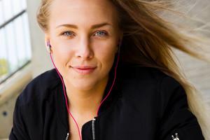 Close Portrait of Blonde Woman In Sportswear Listening To Music