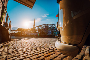 Close-up detail of retro style car on the cobbled square. Arch bridge over canals with Sankt Katherine church in the background. Speicherstadt of Hamburg. Warm sunset and blue sky