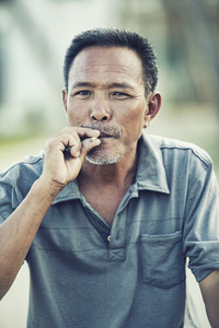 close up face of asian senior man with dry leaves cigarette looking to camera