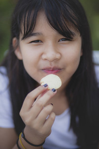 close up face of asian teenager eating snack food with happiness face