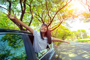 close up face of asian teenager happiness emotion in personal car against green environment of urban town street