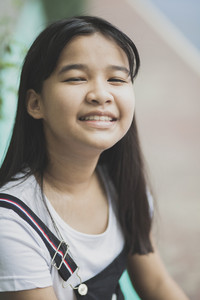 close up face of asian teenager laughing with happiness emotion