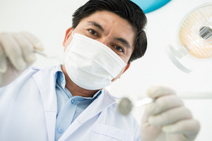 Close-up image of a dentist leaning over a patient to examine thoroughly, subjective pov