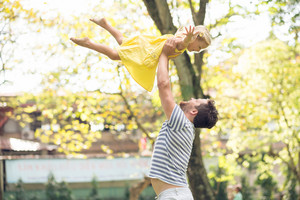 Close-up image of a father throwing his little daughter up in the park