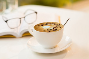 Close-up image of a latte cup with a spoon on a table, a book and eyeglasses on the foreground