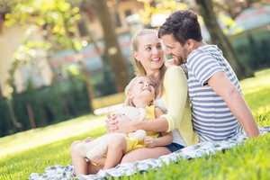 Close-up image of a young cheerful family resting in the park