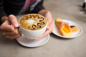 Close-up image of female hands holding a cup of latte coffee on the foreground