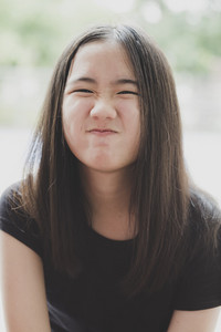 close up kidding face of cheerful asian teenager with long brown hair