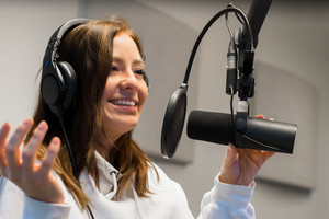 Close-up of a Female Jockey Communicating On Microphone In Radio Studio
