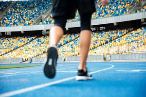 Close up of a male legs in sneakers on a recetrack at the stadium