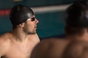 Close up of a male swimmer in cap and swimming goggles looking away