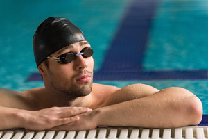 Close up of a male swimmer wearing goggles and swimming cap resting on the edge of a swimming pool