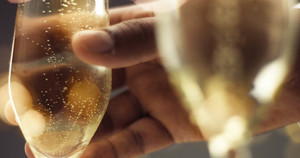 Close up of a man's hand picking up a flute glass with sparkling wine with bubbles in gray and gold tones
