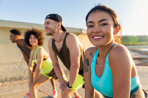 Close up of a smiling sporty woman doing sports with a group of friends outdoors