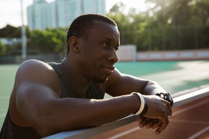 Close up of a young african sportsman leaning on the railing and resting after workout at the stadium