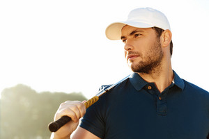 Close up of a young handsome male golfer holding golf club and looking away