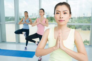 Close-up of a young woman practicing yoga in the aerobics class