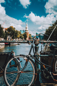 Close-up of Bike parked on a bridge in Amsterdam, Netherlands. Typical cityscape with Amstel river and motion clouds at the background