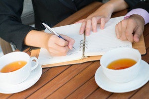 Close-up of colleagues planning their daily business activity over tea