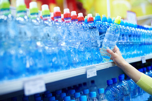 Close-up of female choosing good mineral water in a shop