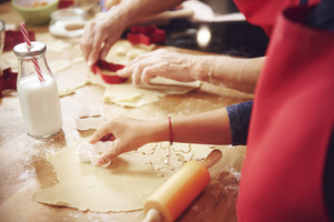 Close Up of human hand cutting cookies out