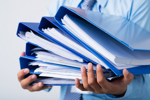 Close-up of human hands holding a stack of folders with business documents on the foreground