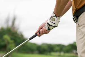 Close-up of male hands holding a golf-iron and ready to play