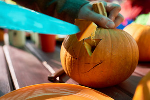 Close-up of man carves details of a jack o' lantern on Halloween