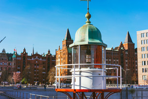 Close up of old beacon lighthouse and red brick building in background, Hafencity - Speicherstadt in Hamburg, Germany