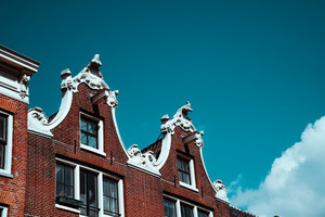 Close-up of old building facade and roof decoration against blue sky in Amsterdam. Architectonic Details Northern Netherlands
