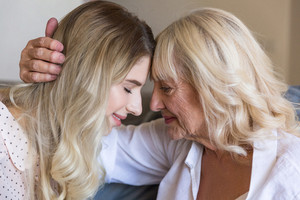Close up of senior grandmother embracing her granddaughter with eyes closed indoors