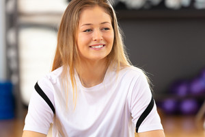 Close-up of smiling portrait of a resting woman at fitness center