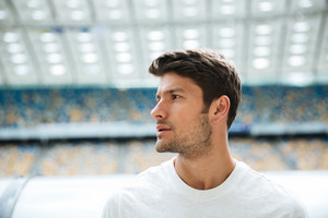 Close up portrait of a handsome sportsman looking away with stadium on a background