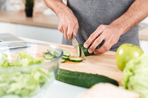 Close up portrait of a man cooking in the kitchen and slicing vegetables on a chopping board