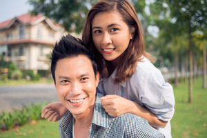 Close-up portrait of a young couple smiling and looking at camera